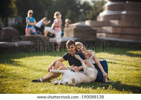 Boy and girl with dog lay on grass - stock photo