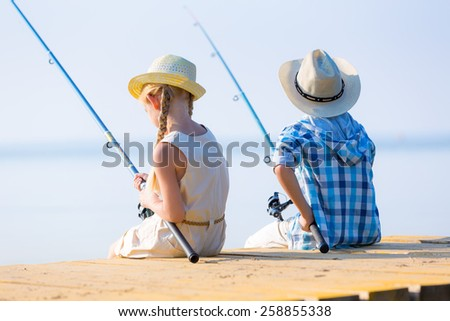 Boy and girl with fishing rods fishing together from a pier - stock photo