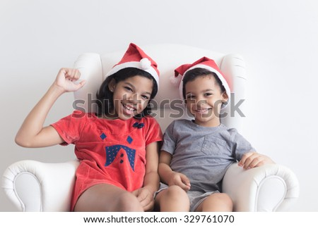 Boy and girl with santa hat / Boy and girl celebrating Christmas