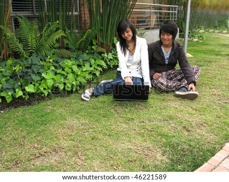 Boy and girl working on laptop in nature