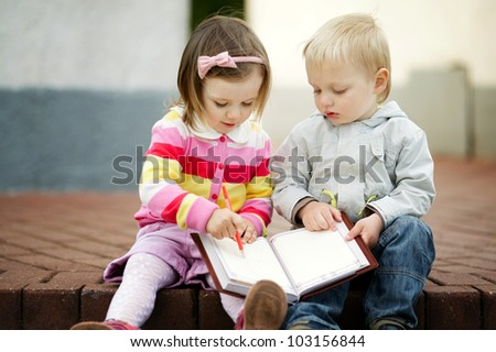 boy and girl writing to notebook - stock photo