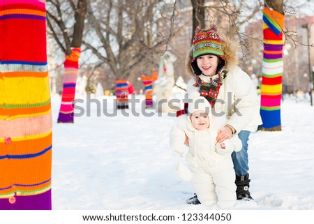 Boy and his baby sister walking between colorful decorated trees in a snowy park - stock photo