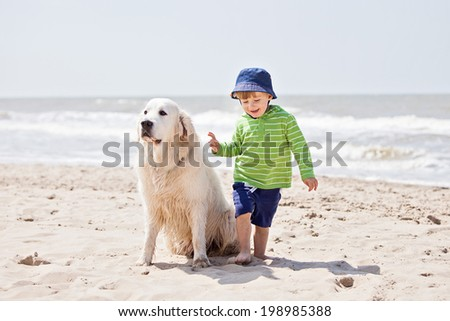 Boy and his dog having fun on a beach  - stock photo