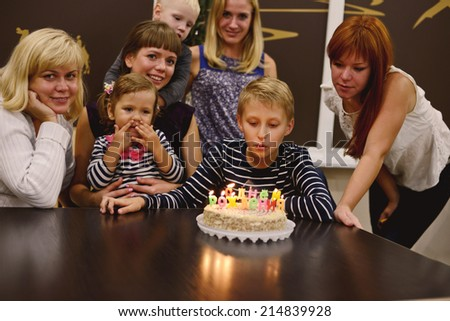boy and his family in his birthday in light of candles