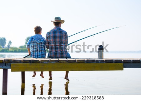 boy and his father fishing together from a pier - stock photo
