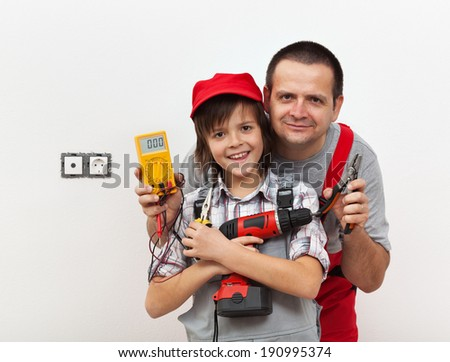 Boy and his father ready for some electricity work - against white wall - stock photo