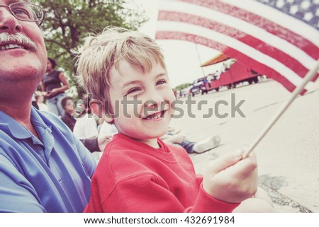 Boy and his father watching a parade - stock photo