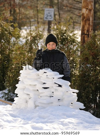 Boy and his winter fortress - stock photo