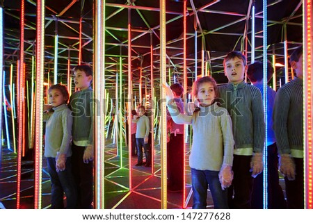 Boy and his younger sister wander in semidarkness of mirror labyrinth - stock photo