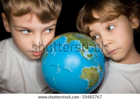 boy and little girl in white T-shirts steadfastly looking at globe of world isolated on black background