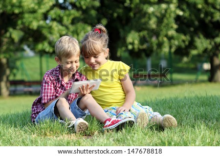 boy and little girl play with tablet pc  - stock photo