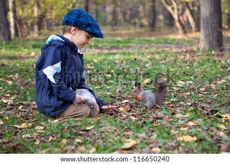 Boy  and little squirrel in autumn park - stock photo