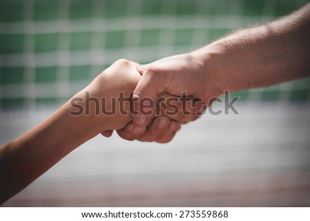 boy and man shaking hands on the background grid
