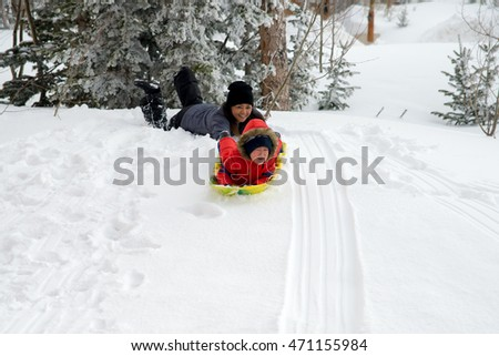 Boy and Mom having a sledding lesson