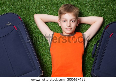 Boy and siutcases th lying on green grass close up
