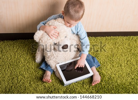 Boy and teddy bear with tablet computer, Top view - stock photo