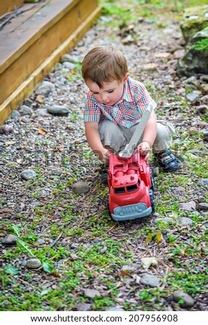Boy and Toy Fire Truck series -  A toddler playing with a toy fire truck outside in the summer.    - stock photo
