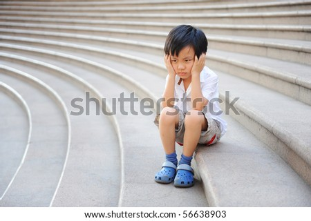 Boy angry and frustrated on the stairs - stock photo
