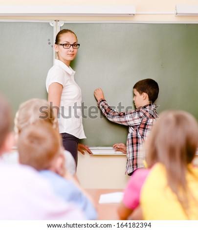 boy answers questions of teachers near a school board - stock photo