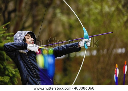 Boy archer shooting with his bow at an outdoor archery range - stock photo