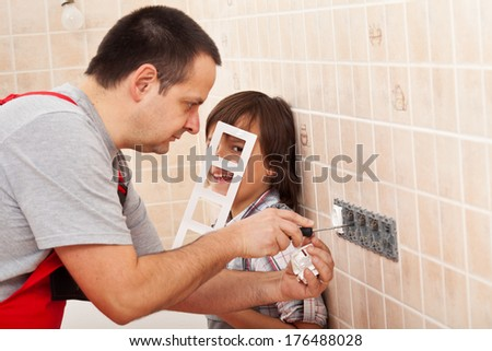 Boy assisting his father in electrician work having fun at the process - focus on child - stock photo