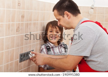 Boy assisting his father installing electrical outlets - happy times together - stock photo