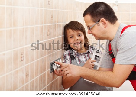 Boy assisting his father installing electrical wall fixtures - holding front panel, copy space - stock photo
