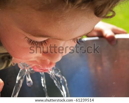 Boy at drinking fountain. - stock photo