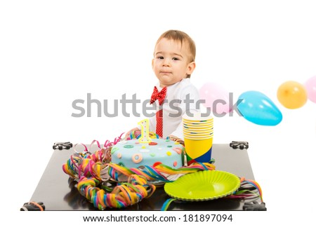 Boy at first anniversary with colorful cake and balloons standing at table isolated on white background - stock photo