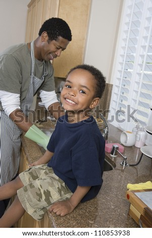 Boy At Kitchen With Father Washing Dishes - stock photo