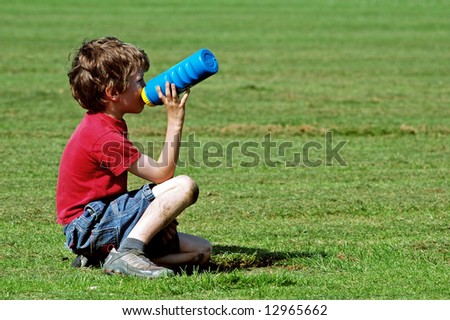 boy at park having a drink - stock photo
