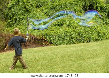 Boy at play creating giant soap bubble - stock photo