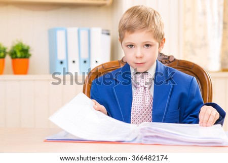 Boy at the desk looking through a folder. - stock photo