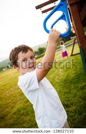 Boy at the rings in a playground - stock photo