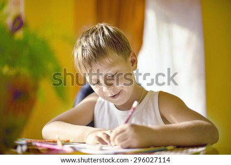 boy at the table draws with crayons concentrated in thought