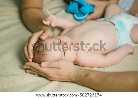 Boy baby laying in diaper and his head into parents mother and father hands