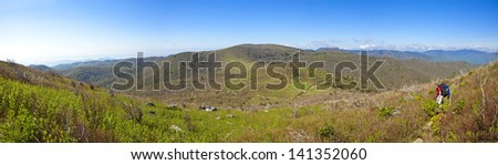 boy backpacking in the mountains, 180 degree panorama - stock photo
