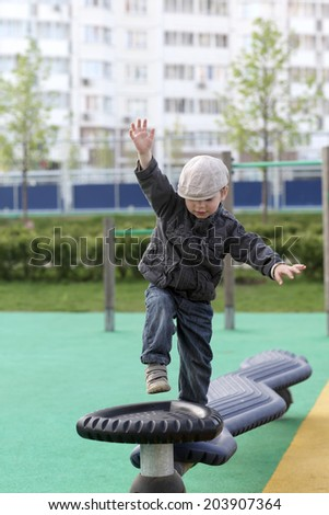 Boy balancing on a sports equipment at outdoor playground - stock photo