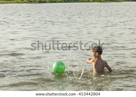 boy bathes in the summer on the river with the ball - stock photo