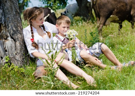 boy & beautiful young woman girl & cows on summer green outdoors background - stock photo