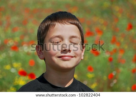 boy blinks from the sun on a blossoming meadow - stock photo