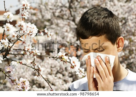 boy blowing his nose and suffering from hay fever. - stock photo