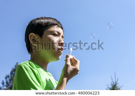 Boy blows small bubbles.
