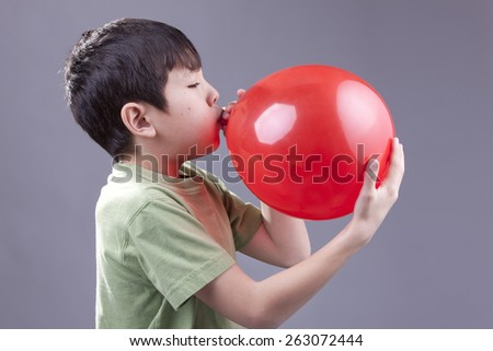 Boy blows up balloon. - stock photo