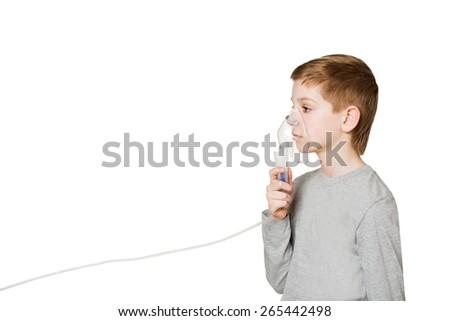 Boy breathing through inhalator mask isolated on white - stock photo