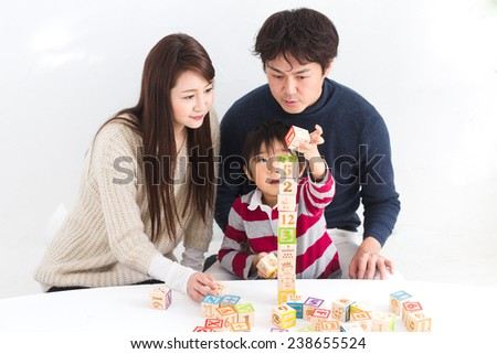 Boy building a tower of wooden blocks with his parents by his side
