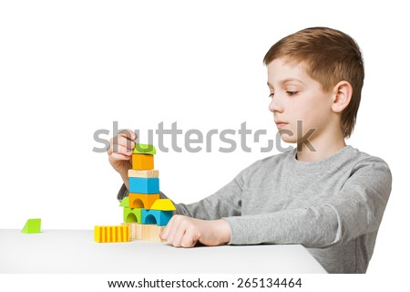Boy building house made of wooden blocks - stock photo