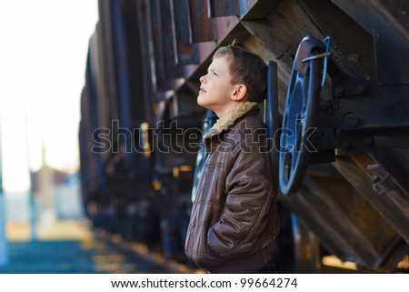 boy bum blonde in brown jacket and crumpled jeans on street near car look up - stock photo