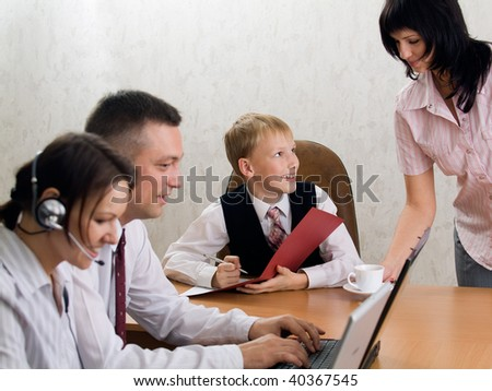 Boy-chief with a group of office workers signing papers