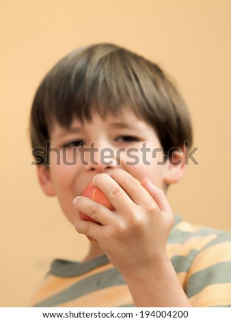 boy child eating an apple holding it up